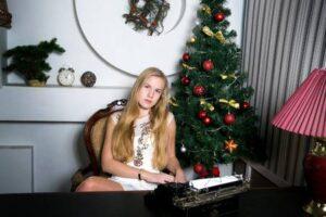 chica rubia guapa en escritorio con arbol de navidad de fondo